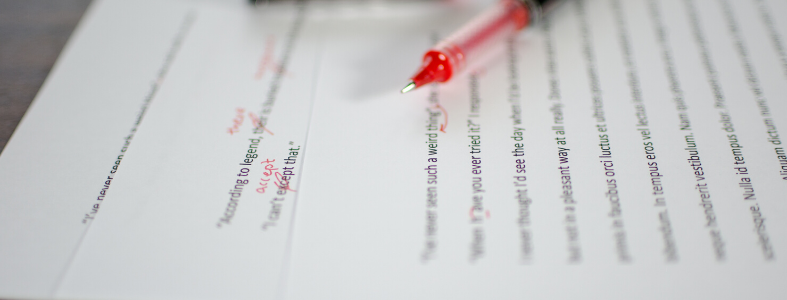 red pen marking up edits on essay