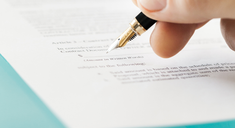 person signing contract on paper